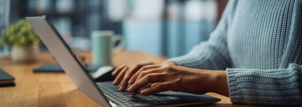 kobieta pisząca na klawiaturze laptopa