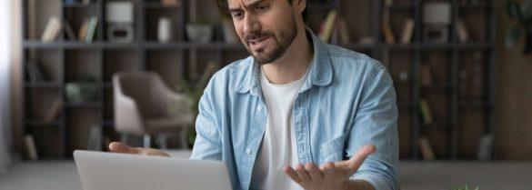 mężczyzna przy zepsutym laptopie